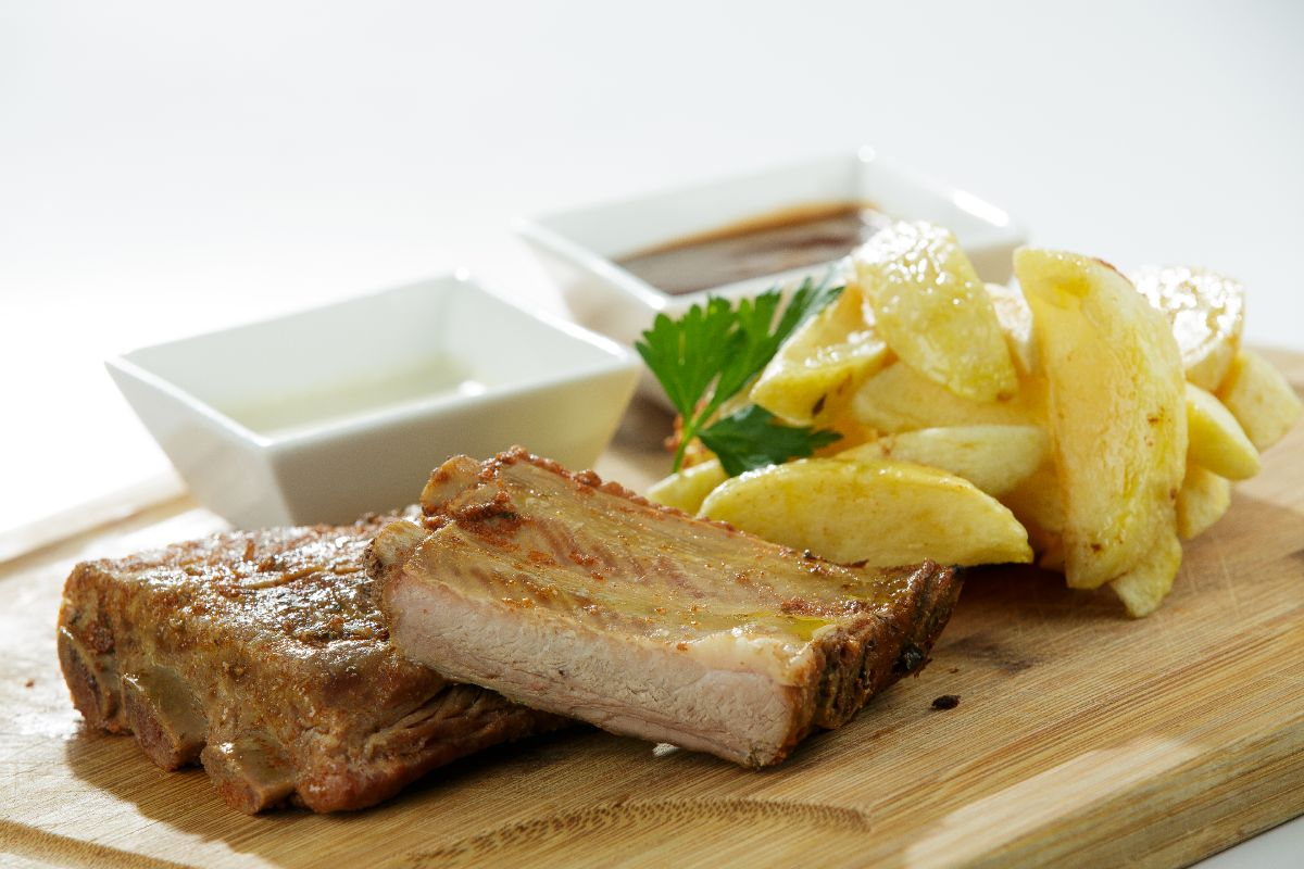 Slowly roasted pork ribs with oven roasted potato wedges with rosemary