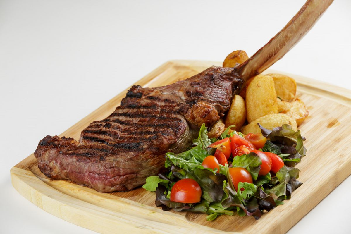 Black Angus Tomahawk beef steak, served with mixed salad leaf and whole backed potatoes with rosemary. Dish for 2 people